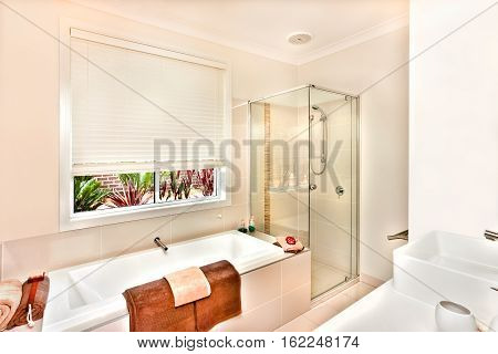 Luxury washroom prepared with towels and soap in the white color bath tub bathing area covers with the glass room next to the water tub. A washstand from the right side