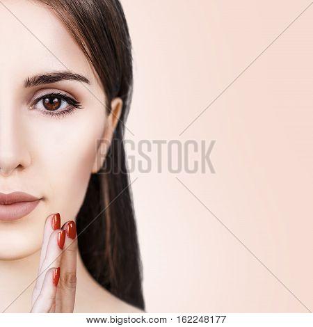 Half-face portrait of beautiful sensitive woman over beige background
