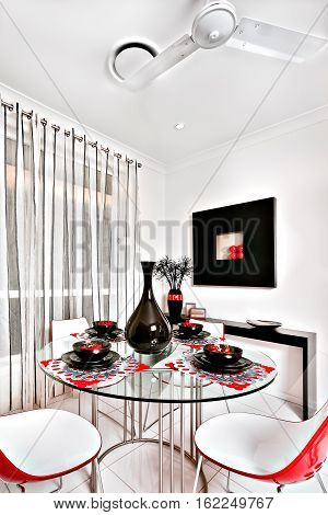 Dining room of a luxurious house chairs are curved and in red. The round table is made of glass and there is a shiny black vase with mugs and dishes on it a small black table can be seen behind the dining area