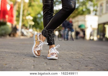 Modern woman in shinny sneakers in the city