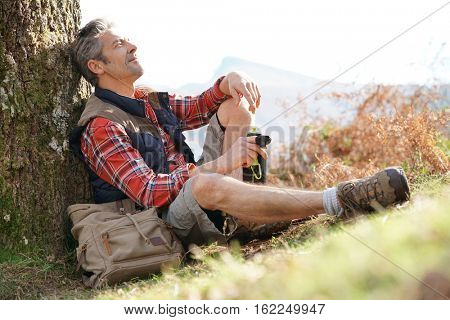 Hiker relaxing by tree on a fall journey