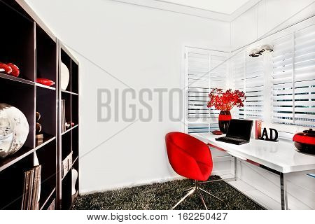 Work room walls are white and floor has a wool carpet. The chair is red. A wooden shelf with items the table is white near to the window. A laptop and shiny vases with flowers can be seen on the table with other ornamental items