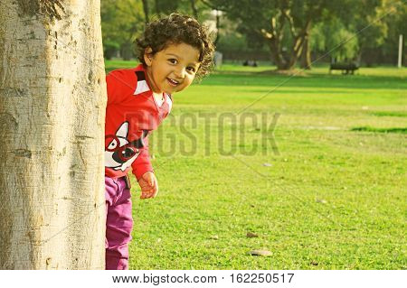 Adorable happy kid with curly hair peeking around the tree playing hide and seek in a park at summer evening