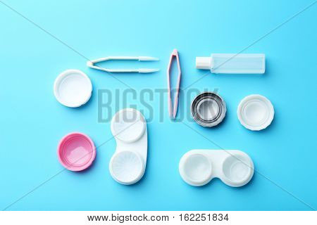 Containers for contact lenses, tweezers and bottle of solution on blue background, close up view