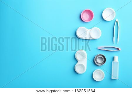 Containers for contact lenses, tweezers and bottle of solution on blue background