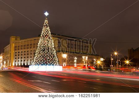 Decorated Christmas tree. Bright lights garlands. The festive mood. Red and gold balloons ribbons and flowers. Lubyanka Square in Moscow. Long exposure