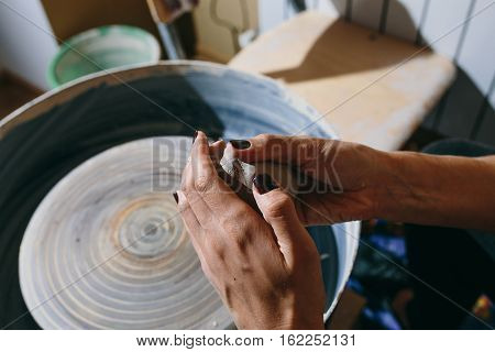 woman holding a ball of clay to make the dishes on the potter's wheel. Woman's hands of making clay pot on the pottery wheel close up. Potter at work.