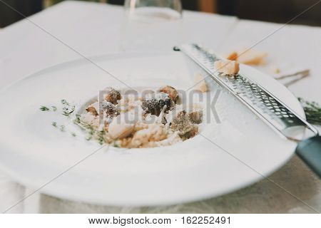 Wild forest mushrooms porcini risotto with rosemary and grated parmesan cheese. Traditional italian cuisine dish. Restaurant food closeup. Shallow depth of field, selective focus