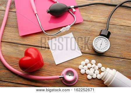 Pink stethoscope, pills and other medical equipment on wooden background