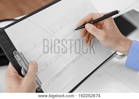 Male doctor making notes on cardiogram, close up view