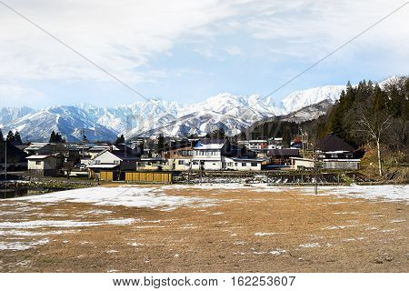 Hakuba mountain range in the afternoon early winter. The steep terrain in the center is between two ski resorts, Happo-One and Goryu. Hakuba village houses and farm land in the foreground are on completely flat terrain.