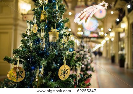 Christmas tree with gold ornaments on background of shopping center
