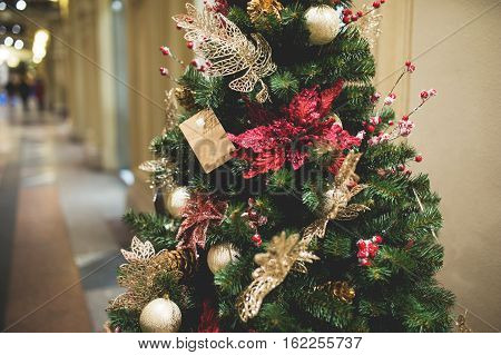 Pine tree decorated with flowers and gifts in lobby of building, toned photo