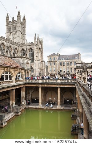 Bath Somerset United Kingdom - June 19 2006: Tourists at the ancient Roman Baths Museum. Bath Abbey and Roman Baths the UNESCO World Heritage site with green water reflection under cloudy sky.