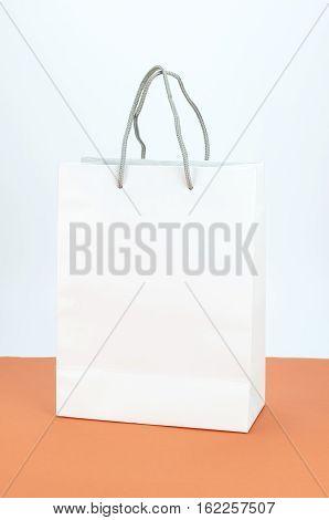 Blank paper white bag on orange and white background.