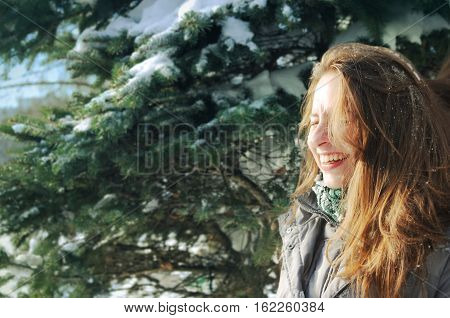 Young Girl Among Spruce Branches In Winter