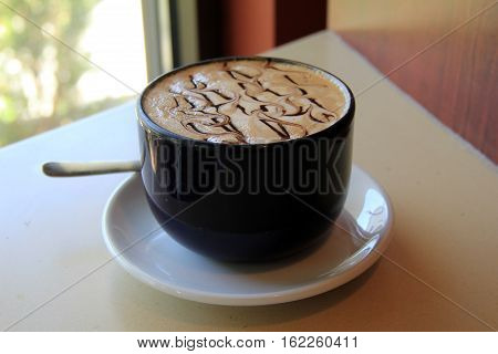 Large blue mug with delicious, steaming hot latte, drizzle of  dark chocolate syrup over the top.