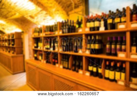 Blurred wine cellar background with bottles on wooden shelfs in vintage authentic store interior
