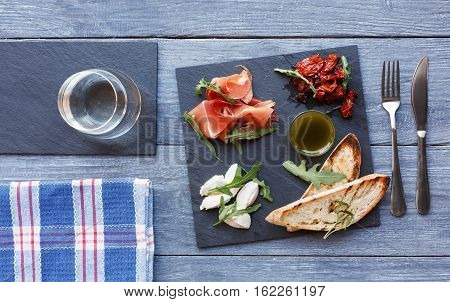 Catering platter antipasto with ham prosciutto, bruschetta bread toasts and mozzarella cheese on stone desk on blue wood served table top view. Served starter meals, restaurant food