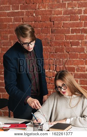 Teacher correct student writing in copybook. Beautiful girl looking at camera while man standing above her, looking at her notebook, free space for text