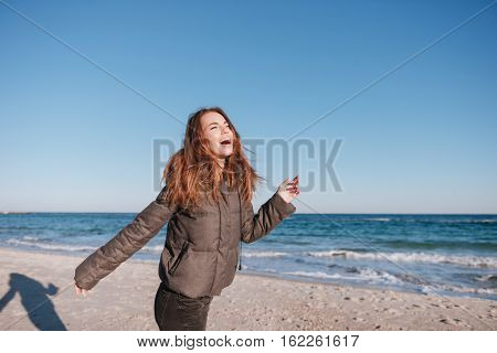 Laughing Woman dressed in warm jacket on date on beach near the sea. Side view
