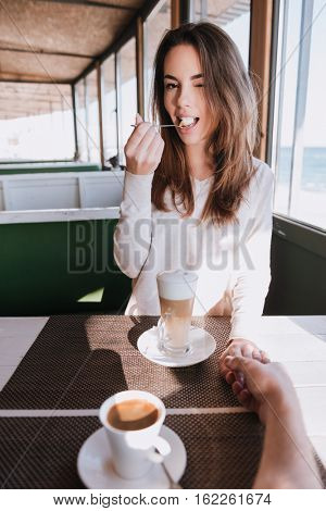 Vertical image of pretty woman on date with coffee in cafe near the sea. First-person view