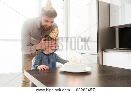 Picture of cheerful bearded young father in the kitchen with his birthday little son covering his eyes.