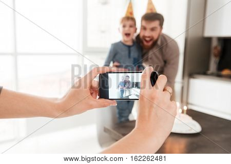 Photo of smiling bearded young father in the kitchen with his birthday little son making selfie