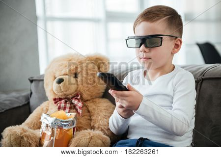 Photo of cute little boy wearing 3d glasses sitting on sofa with teddy bear at home and watching TV while eating chips. Holding remote control.