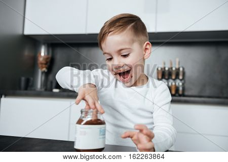 Photo of happy boy standing in the kitchen while eating sweeties. Look at sweeties.