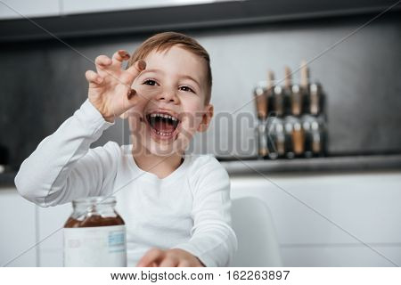 Picture of happy boy standing in the kitchen while eating sweeties. Look aside.