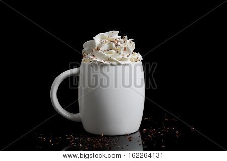 cup of hot chocolate with whipped cream on black background
