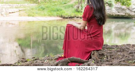 Woman Sitting Next To A River Alone