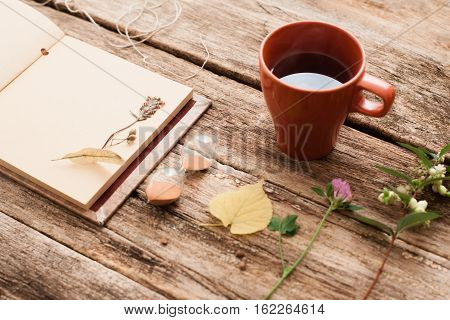 Vintage album with herbarium plants and hourglass with cup of tea on old wooden background. Transience of time, memory, nostalgia, art, hobby concept