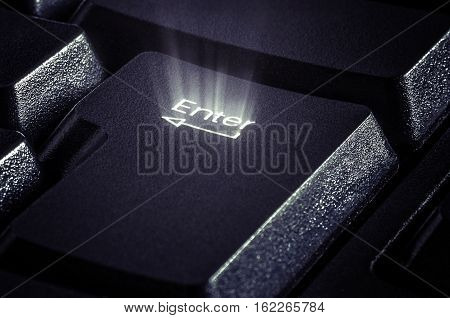 Image of key closeup with rays emanating from the word Enter. The concept of online sales and purchases selection start and etc..