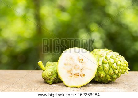 Noni fruit and noni slice on wooden table and green background.Fruit for health and herb for health.14
