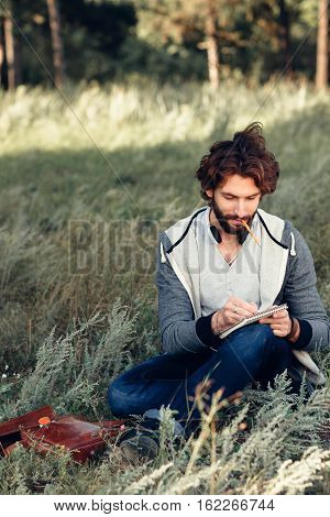 Artist sketching in notebook outdoor, free space. Attractive man painter drawing picture in sketchbook. Inspiration of nature, art, hobby, rest concept