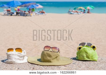 Hats and sunglasses on the beach. Family holiday