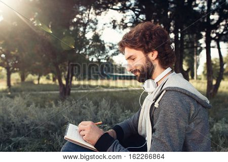 Young man writing in notebook at nature, side view. Profile of bearded man creating composition, free space for text. Art, idea, inspiration concept