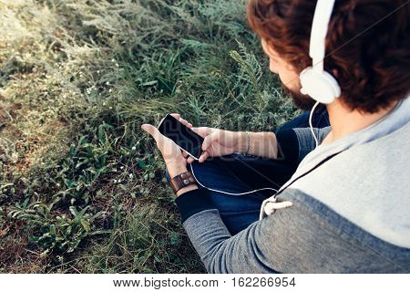 Man choosing music on smartphone outdoor. Top back view on guy listening for favorite song online, mockup, free space on green grass. Leisure, hobby, relax concept