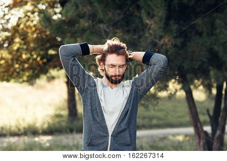 Excited man touching his head in park. Happy man feeling joy, happiness, pleasure of being in forest, free space. Overabundance of emotions, Indian summer, life love, new beginnings concept