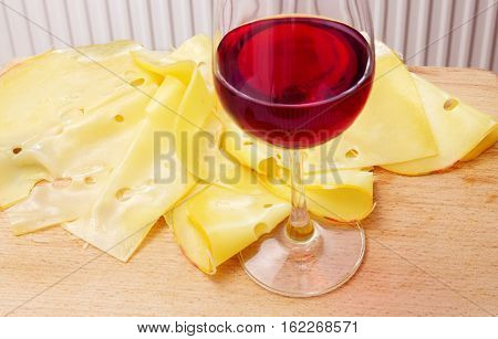 Maasdam cheese and wineglass with red wine on a wooden board