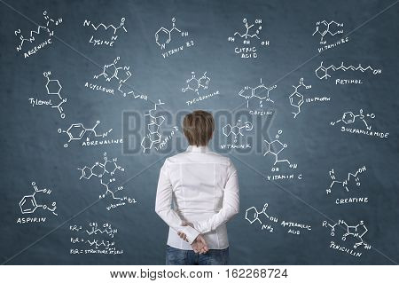 Healthcare worker standing in front of chemistry formula of antibiotics vitamins and food additives. Science concept.