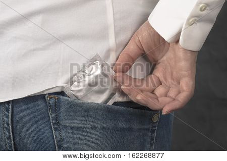 Condom in the pocket of blue jeans. Healthcare and medicine concept