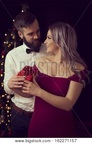 Beautiful young couple in love hugging and exchanging Christmas gifts. Focus on the girl