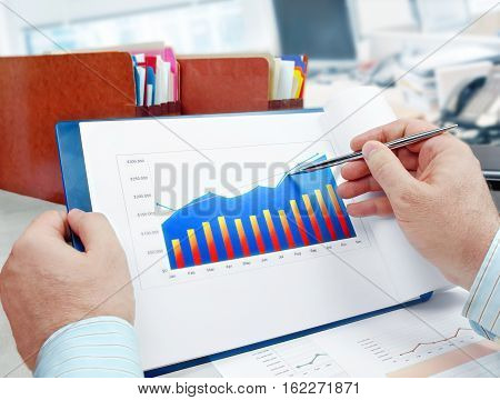 Male hand with pen on the investment chart