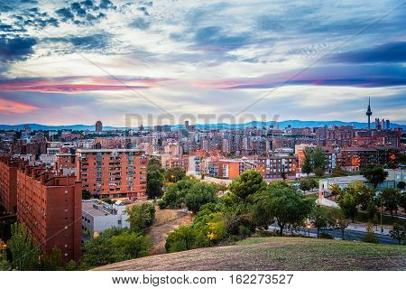 Madrid cityscape at dusk from a residential district and mountain range at background