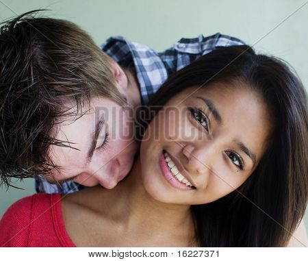 Young couple embrace and kiss in candid happy cute natural moment