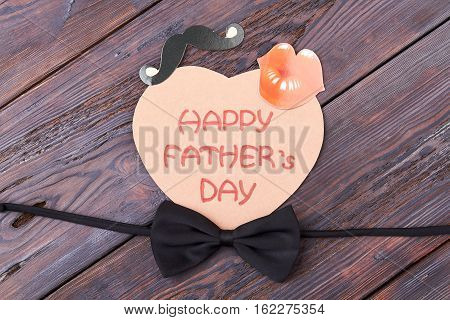 Black bow tie on wood. Card with lips and mustache. How to decorate greeting paper.