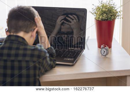 Shocked Boy With Glasses Using Laptop Computer While Sitting On Desk At Home. Expressive Face In Ref